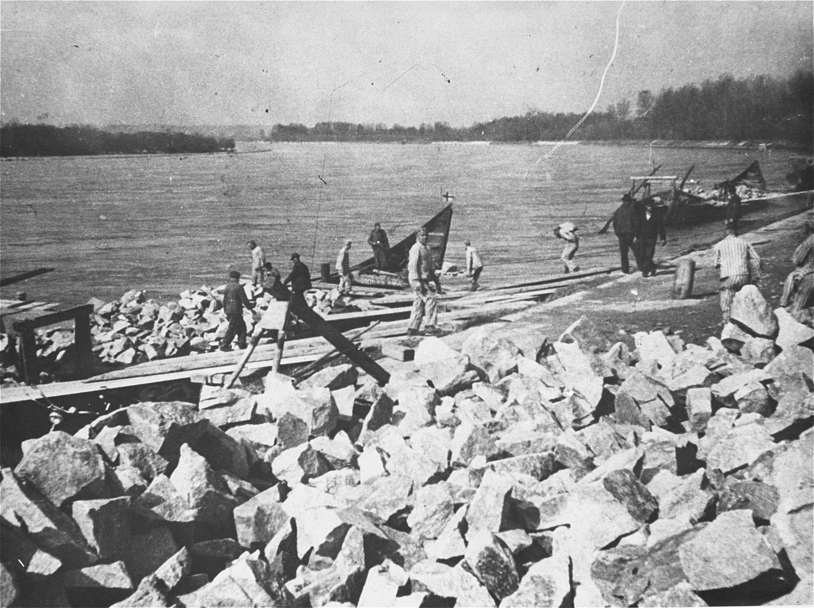 Prisoners at forced labor in the Mauthausen concentration camp loading rocks onto boats in the Danube River.