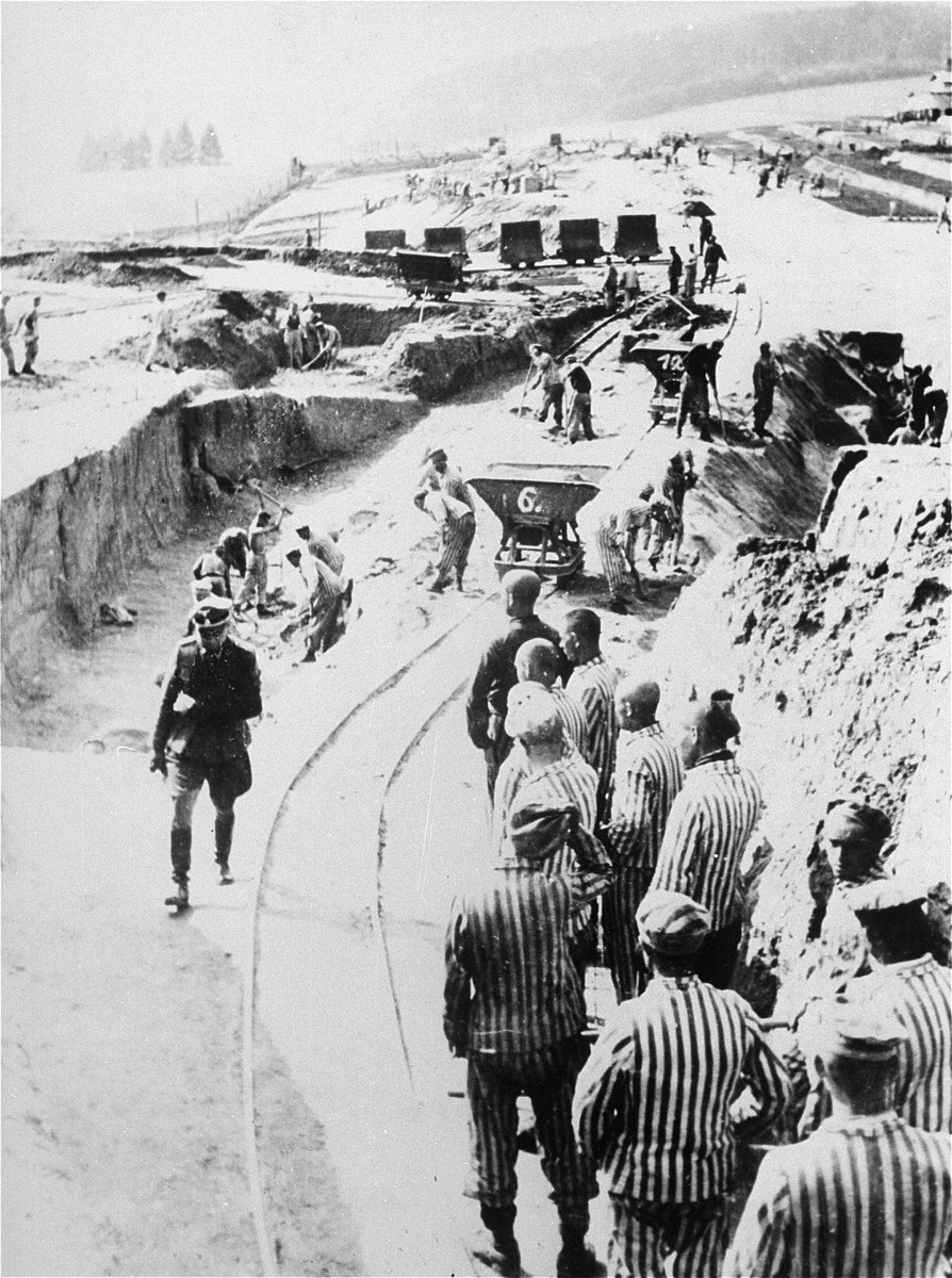 """SS-Hauptsturmfuehrer Georg Bachmaier, deputy to Commandant Franz Ziereis in Mauthausen, inspects a group of prisoners at forced labor constructing the """"Russian camp."""""""