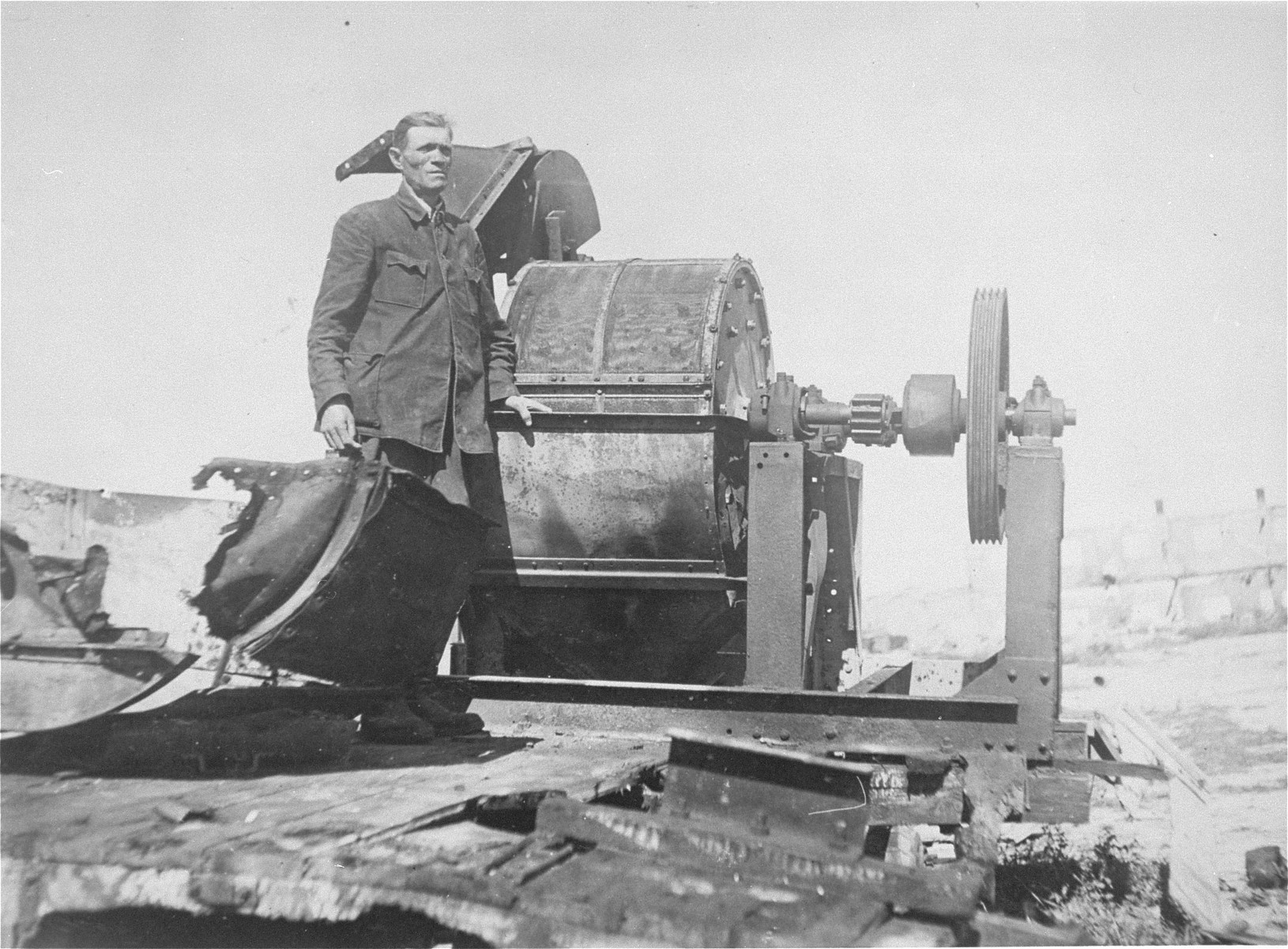 Moses Korn, a Jewish prisoner forced to work in Sonderkommando 1005 unit, poses next to a bone crushing machine in the Janowska concentration camp.  This photograph ws taken soon after liberation for the Extraordinary Commission or the Red Army.