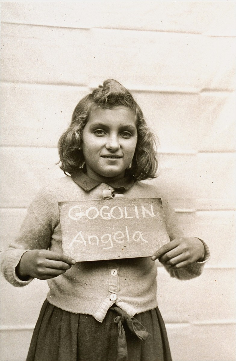 Angela Gogolin holds a name card intended to help any of her surviving family members locate her at the Kloster Indersdorf DP camp.  This photograph was published in newspapers to facilitate reuniting the family.