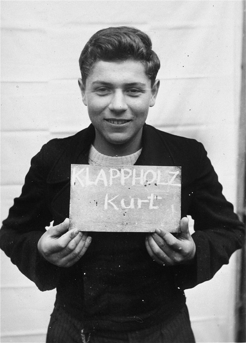Kurt Klappholz holds a name card intended to help any of his surviving family members locate him at the Kloster Indersdorf DP camp.  This photograph was published in newspapers to facilitate reuniting the family.