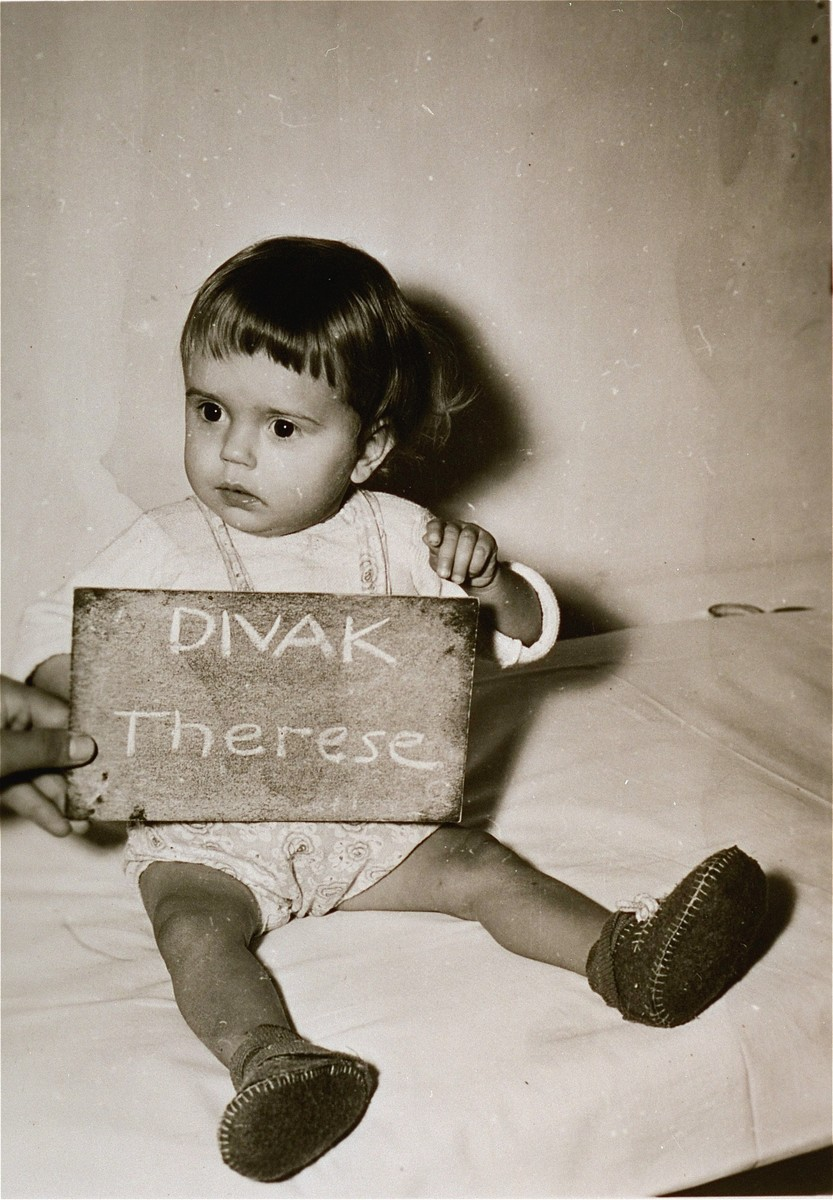 Therese Divak holds a name card intended to help any of her surviving family members locate her at the Kloster Indersdorf DP camp.  This photograph was published in newspapers to facilitate reuniting the family.