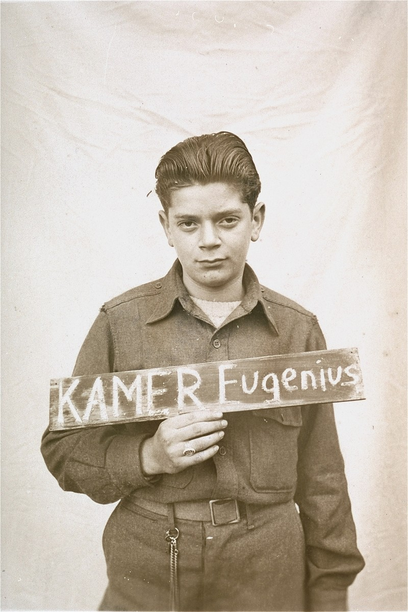 Eugenius Kamer holds a name card intended to help any of his surviving family members locate him at the Kloster Indersdorf DP camp.  This photograph was published in newspapers to facilitate reuniting the family.
