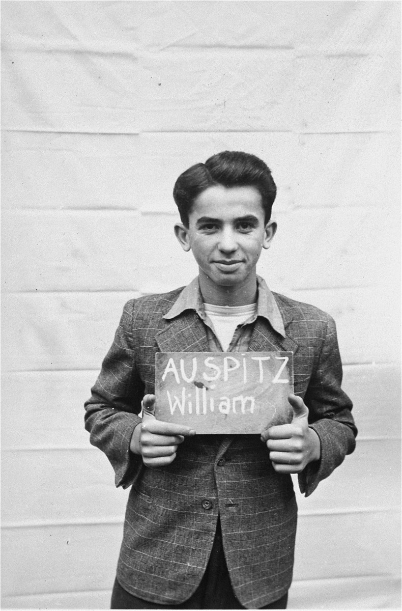 William Auspitz holds a name card intended to help any of his surviving family members locate him at the Kloster Indersdorf DP camp.  This photograph was published in newspapers to facilitate reuniting the family.