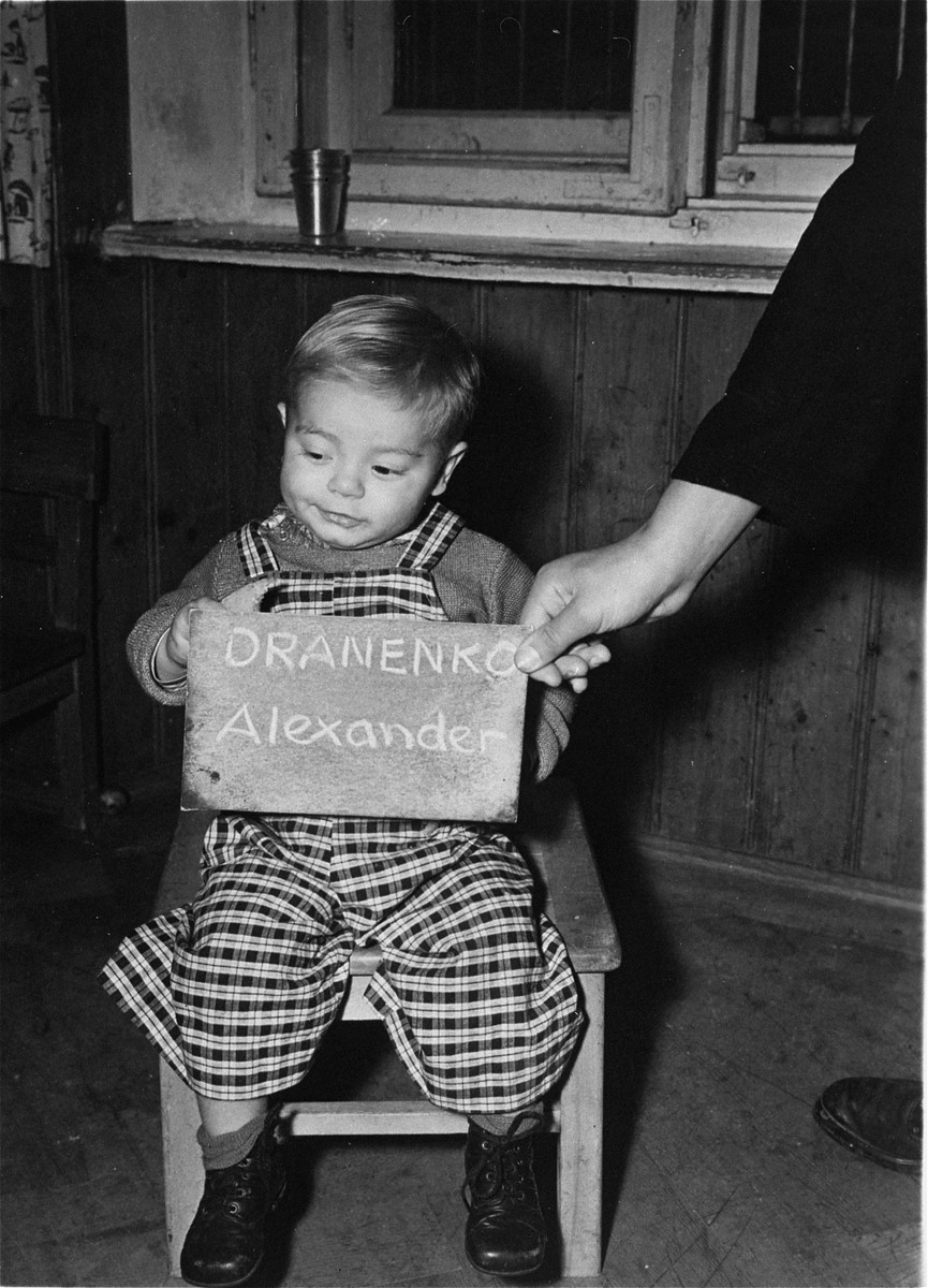 Alexander Dranenko holds a name card intended to help any of his surviving family members locate him at the Kloster Indersdorf DP camp.  This photograph was published in newspapers to facilitate reuniting the family.
