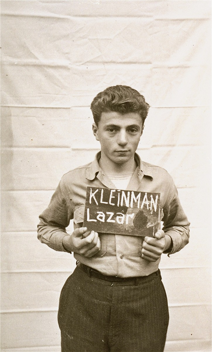 Lazar Kleinman holds a name card intended to help any of his surviving family members locate him at the Kloster Indersdorf DP camp.  This photograph was published in newspapers to facilitate reuniting the family.