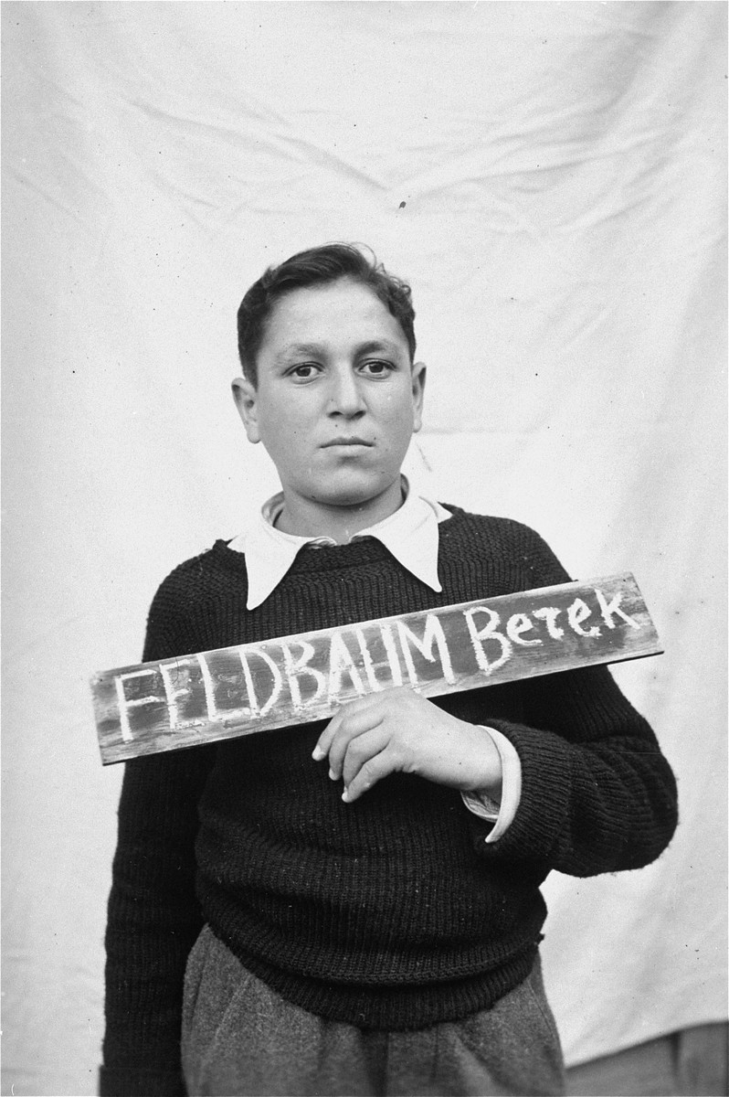 Bezek Feldbaum holds a name card intended to help any of his surviving family members locate him at the Kloster Indersdorf DP camp.  This photograph was published in newspapers to facilitate reuniting the family.