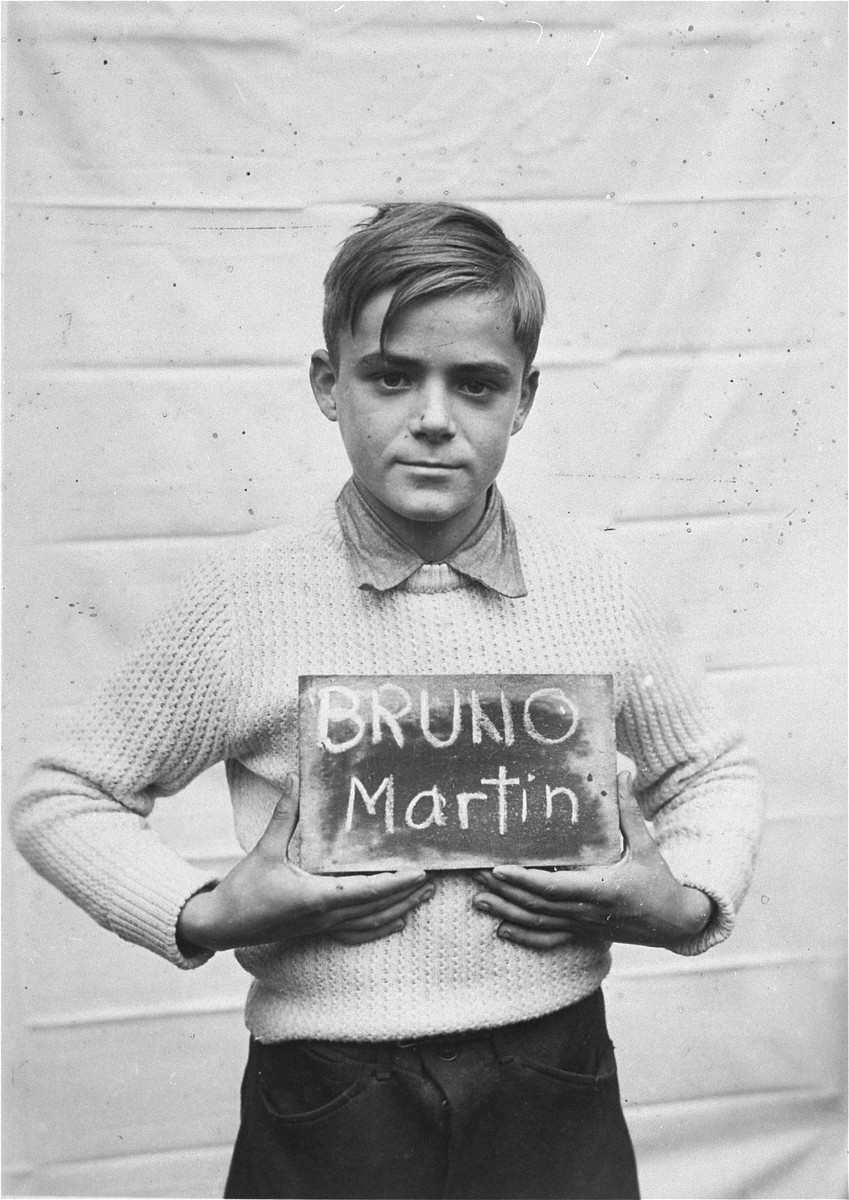 Martin Bruno holds a name card intended to help any of his surviving family members locate him at the Kloster Indersdorf DP camp.  This photograph was published in newspapers to facilitate reuniting the family.