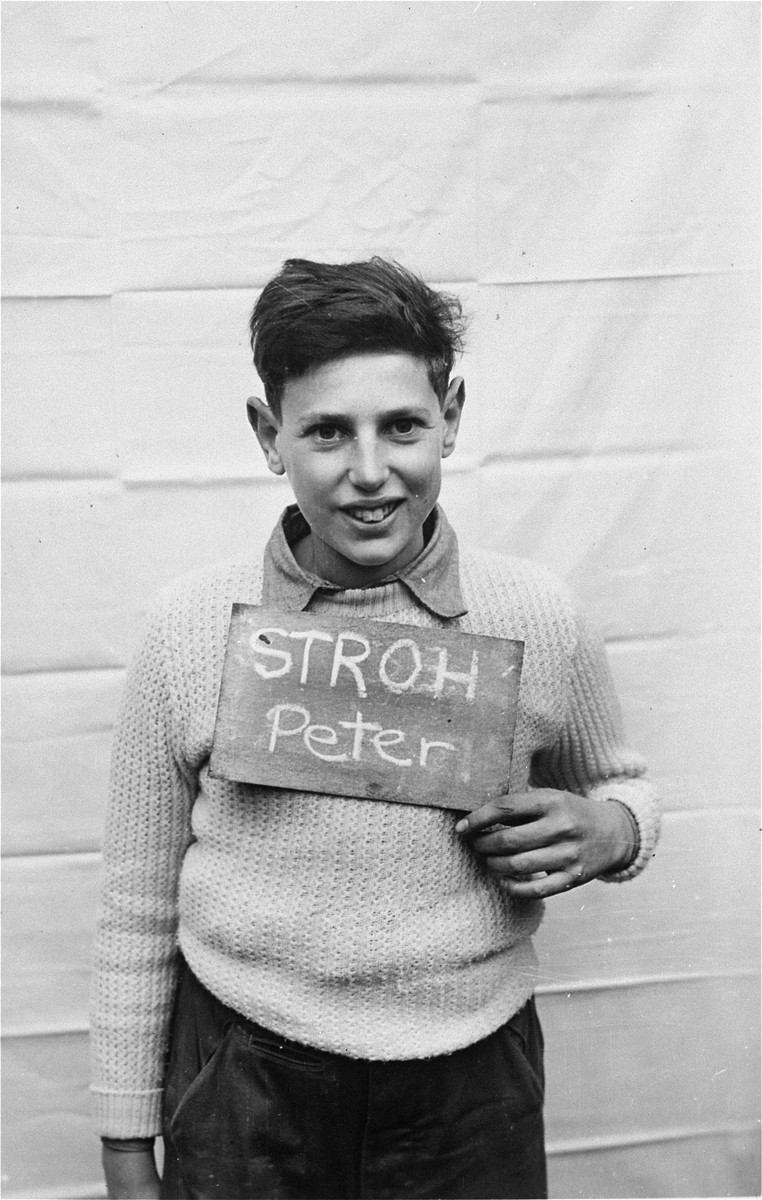 Peter Stroh holds a name card intended to help any of his surviving family members locate him at the Kloster Indersdorf DP camp.  This photograph was published in newspapers to facilitate reuniting the family.