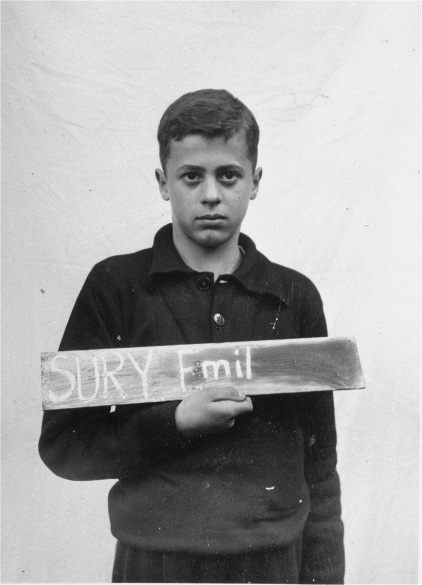 Emil Sury holds a name card intended to help any of his surviving family members locate him at the Kloster Indersdorf DP camp.  This photograph was published in newspapers to facilitate reuniting the family.