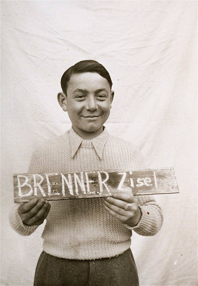 Zisel Brenner holds a name card intended to help any of his surviving family members locate him at the Kloster Indersdorf DP camp.  This photograph was published in newspapers to facilitate reuniting the family.