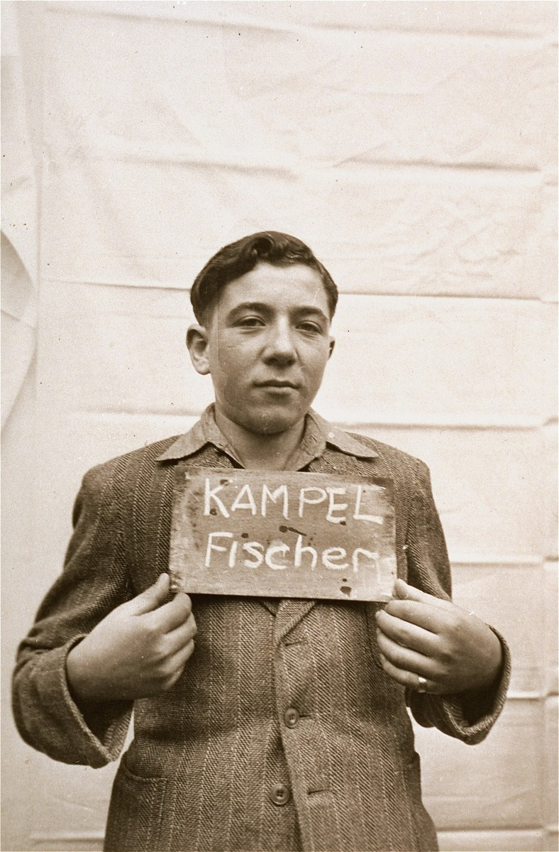 Fischer Kampel holds a name card intended to help any of his surviving family members locate him at the Kloster Indersdorf DP camp.  This photograph was published in newspapers to facilitate reuniting the family.