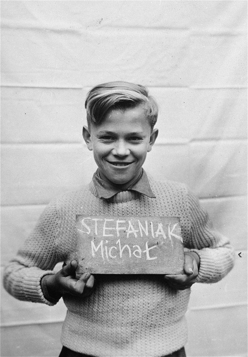 Michal Stefaniak holds a name card intended to help any of his surviving family members locate him at the Kloster Indersdorf DP camp.  This photograph was published in newspapers to facilitate reuniting the family.