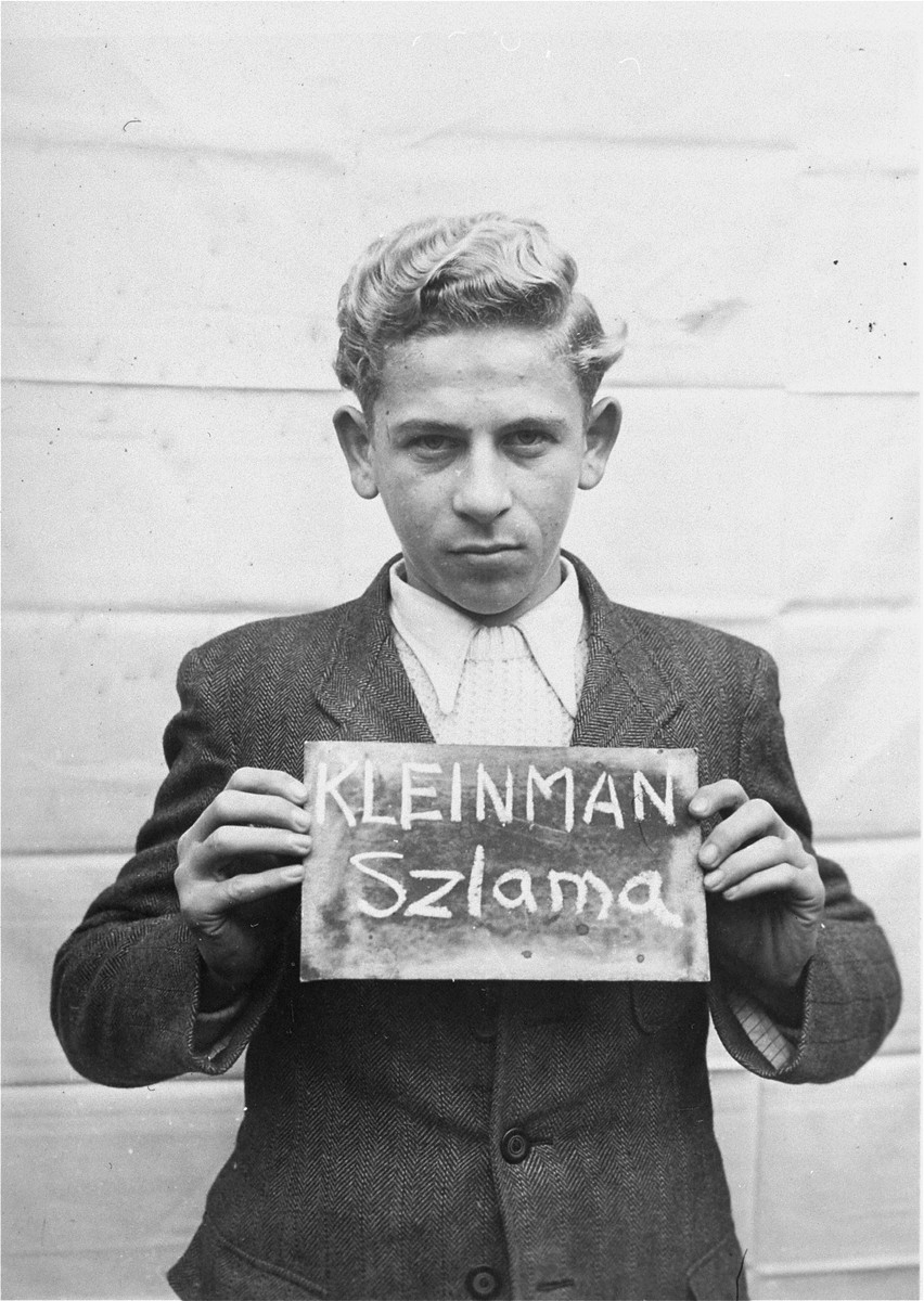 Szlama Kleinman holds a name card intended to help any of his surviving family members locate him at the Kloster Indersdorf DP camp.  This photograph was published in newspapers to facilitate reuniting the family.