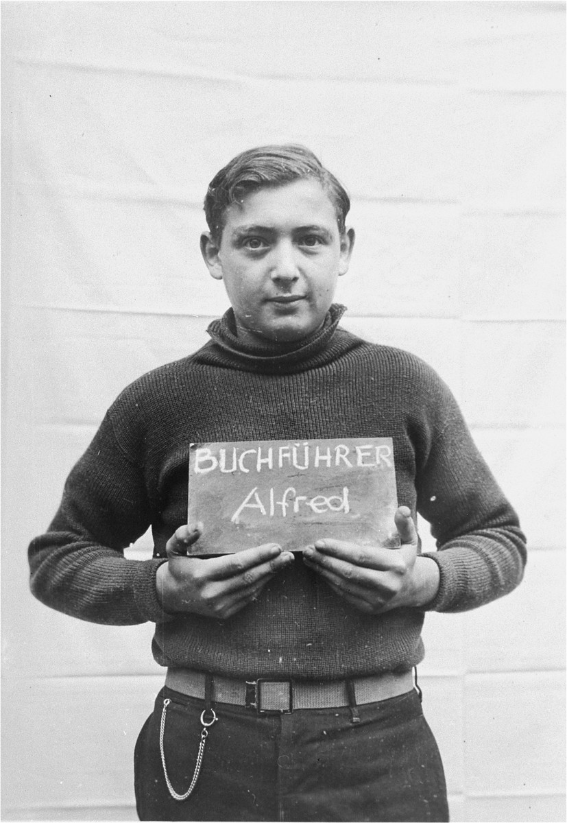 Alfred Buchfuhrer holds a name card intended to help any of his surviving family members locate him at the Kloster Indersdorf DP camp.  This photograph was published in newspapers to facilitate reuniting the family.
