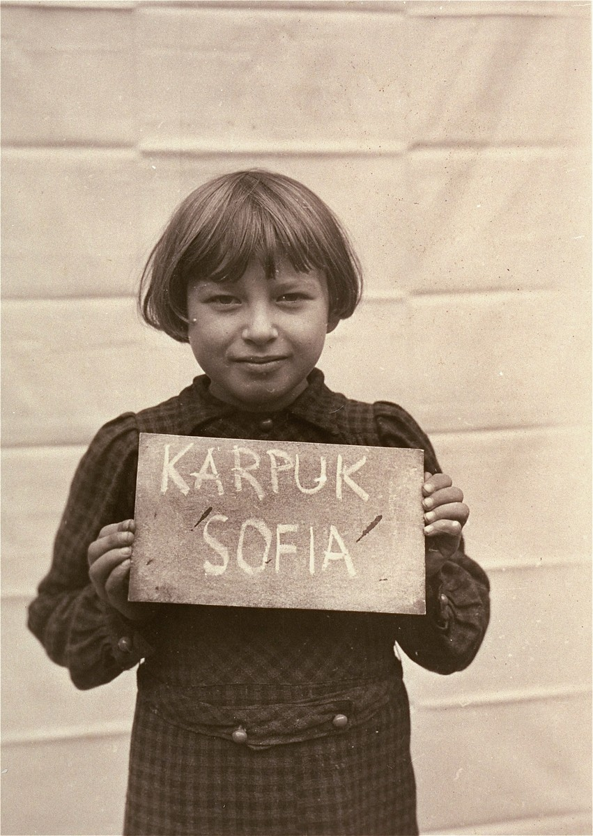 Sofia Karpuk holds a name card intended to help any of her surviving family members locate her at the Kloster Indersdorf DP camp.  This photograph was published in newspapers to facilitate reuniting the family.