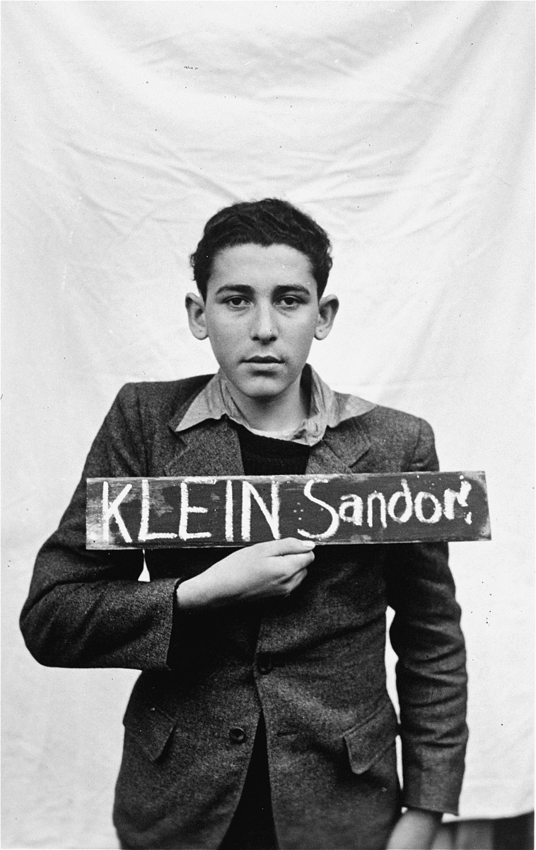 Sandor Klein holds a name card intended to help any of his surviving family members locate him at the Kloster Indersdorf DP camp.  This photograph was published in newspapers to facilitate reuniting the family.