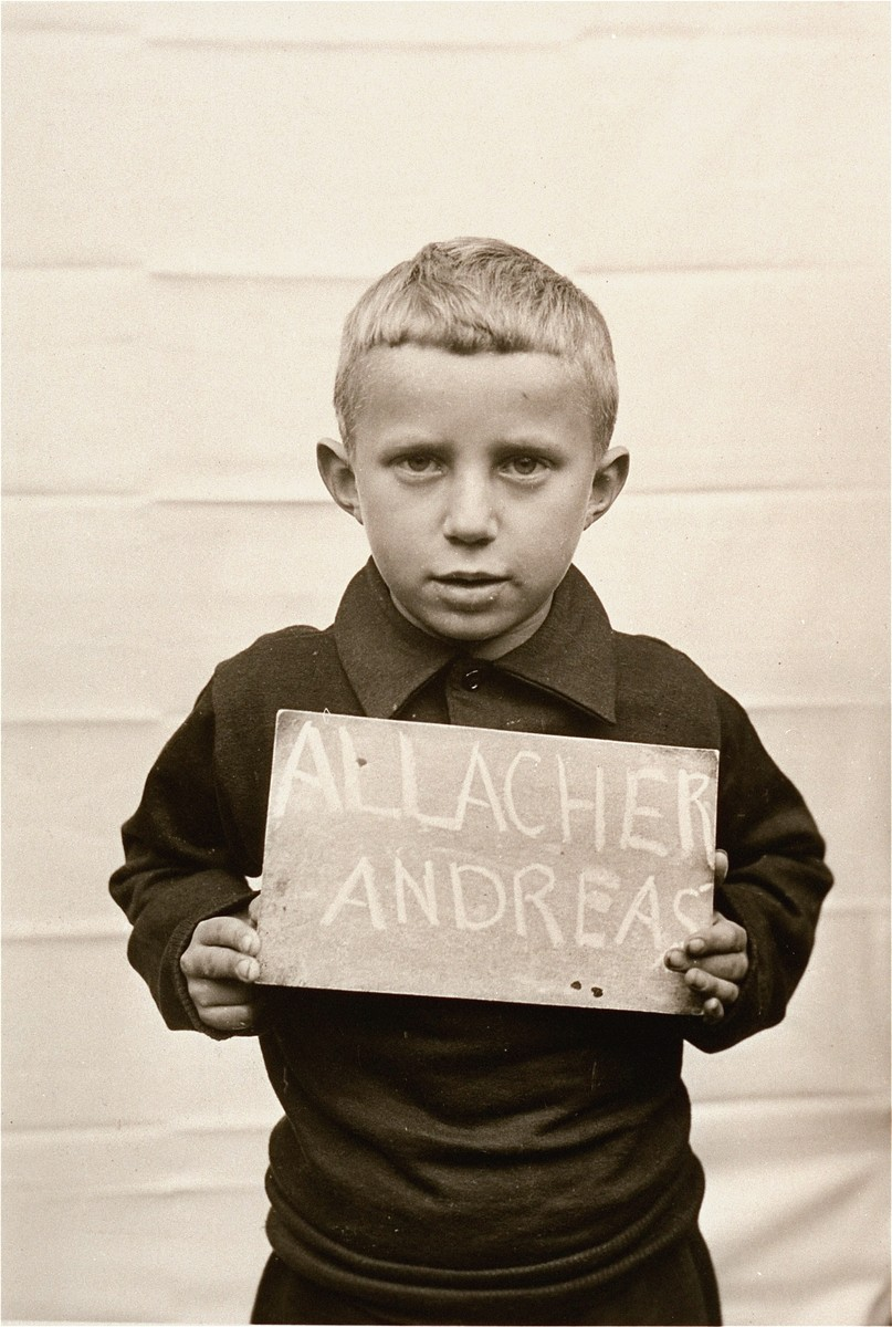 Andreas Allacher holds a name card intended to help any of his surviving family members locate him at the Kloster Indersdorf DP camp.  This photograph was published in newspapers to facilitate reuniting the family.