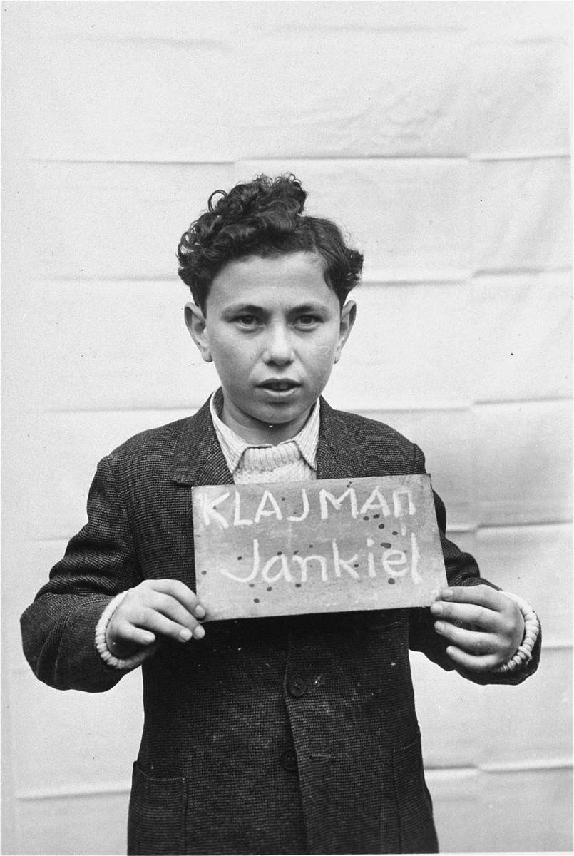 Jankiel Klajman holds a name card intended to help any of his surviving family members locate him at the Kloster Indersdorf DP camp.  This photograph was published in newspapers to facilitate reuniting the family.