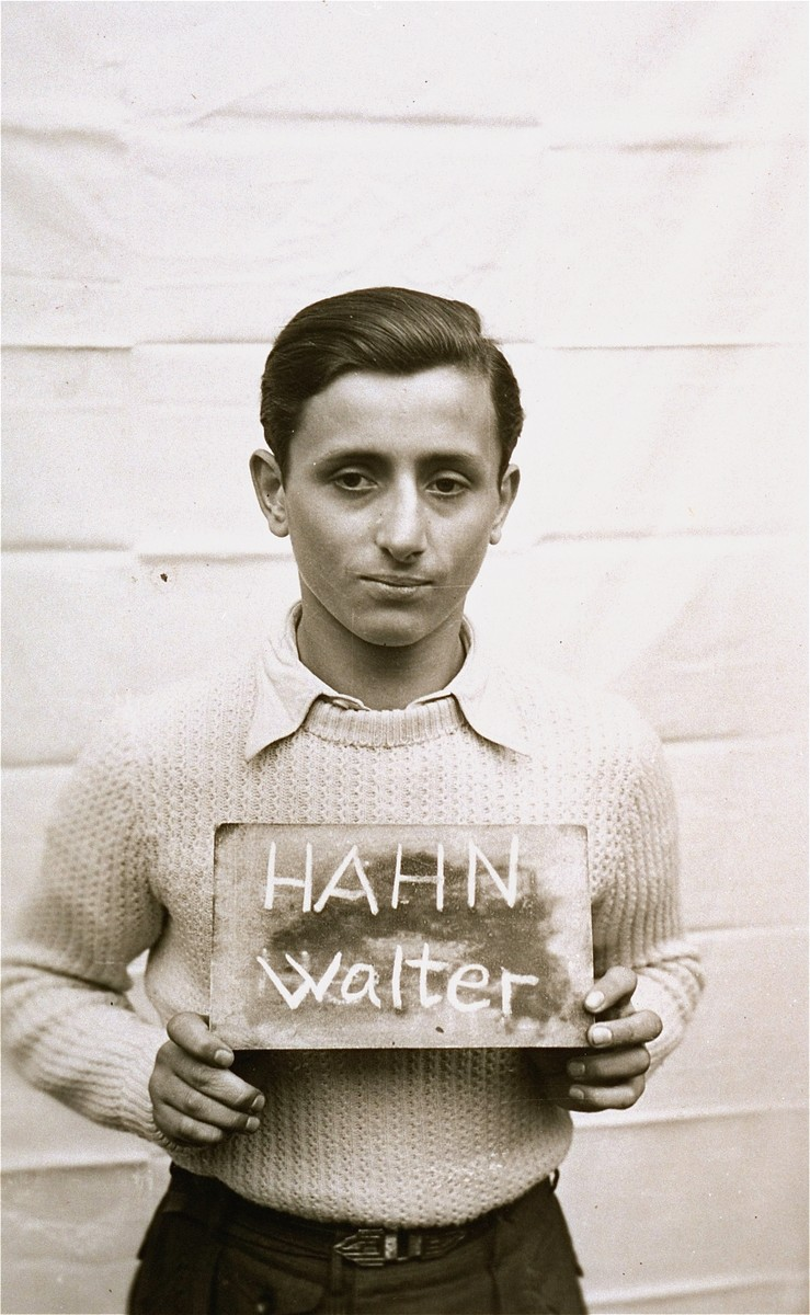 Walter Hahn holds a name card intended to help any of his surviving family members locate him at the Kloster Indersdorf DP camp.  This photograph was published in newspapers to facilitate reuniting the family.
