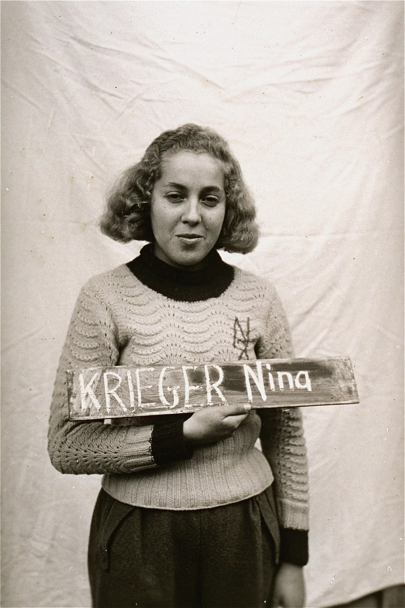 Nina Krieger holds a name card intended to help any of her surviving family members locate her at the Kloster Indersdorf DP camp.  This photograph was published in newspapers to facilitate reuniting the family.