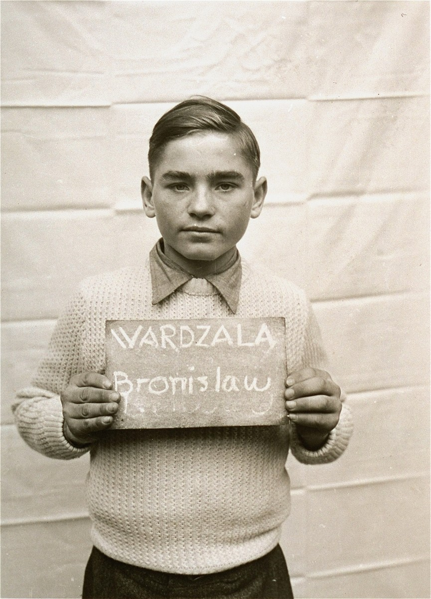 Bronislaw Wardzala holds a name card intended to help any of his surviving family members locate him at the Kloster Indersdorf DP camp.  This photograph was published in newspapers to facilitate reuniting the family.