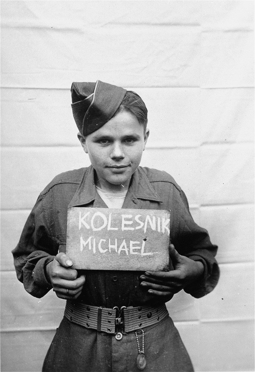 Michael Kolesnik holds a name card intended to help any of his surviving family members locate him at the Kloster Indersdorf DP camp.  This photograph was published in newspapers to facilitate reuniting the family.
