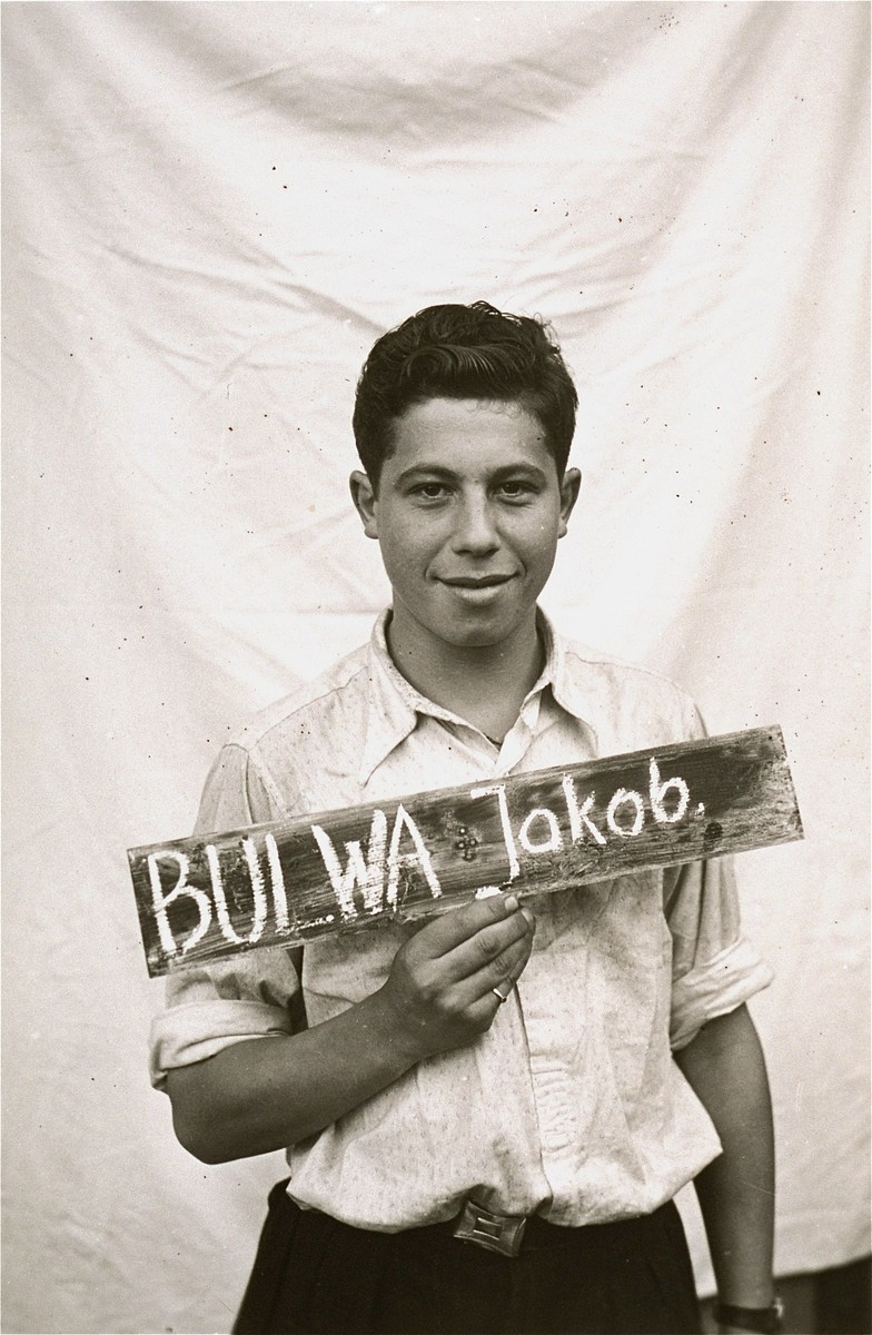 Jakob Bulwa holds a name card intended to help any of his surviving family members locate him at the Kloster Indersdorf DP camp.  This photograph was published in newspapers to facilitate reuniting the family.