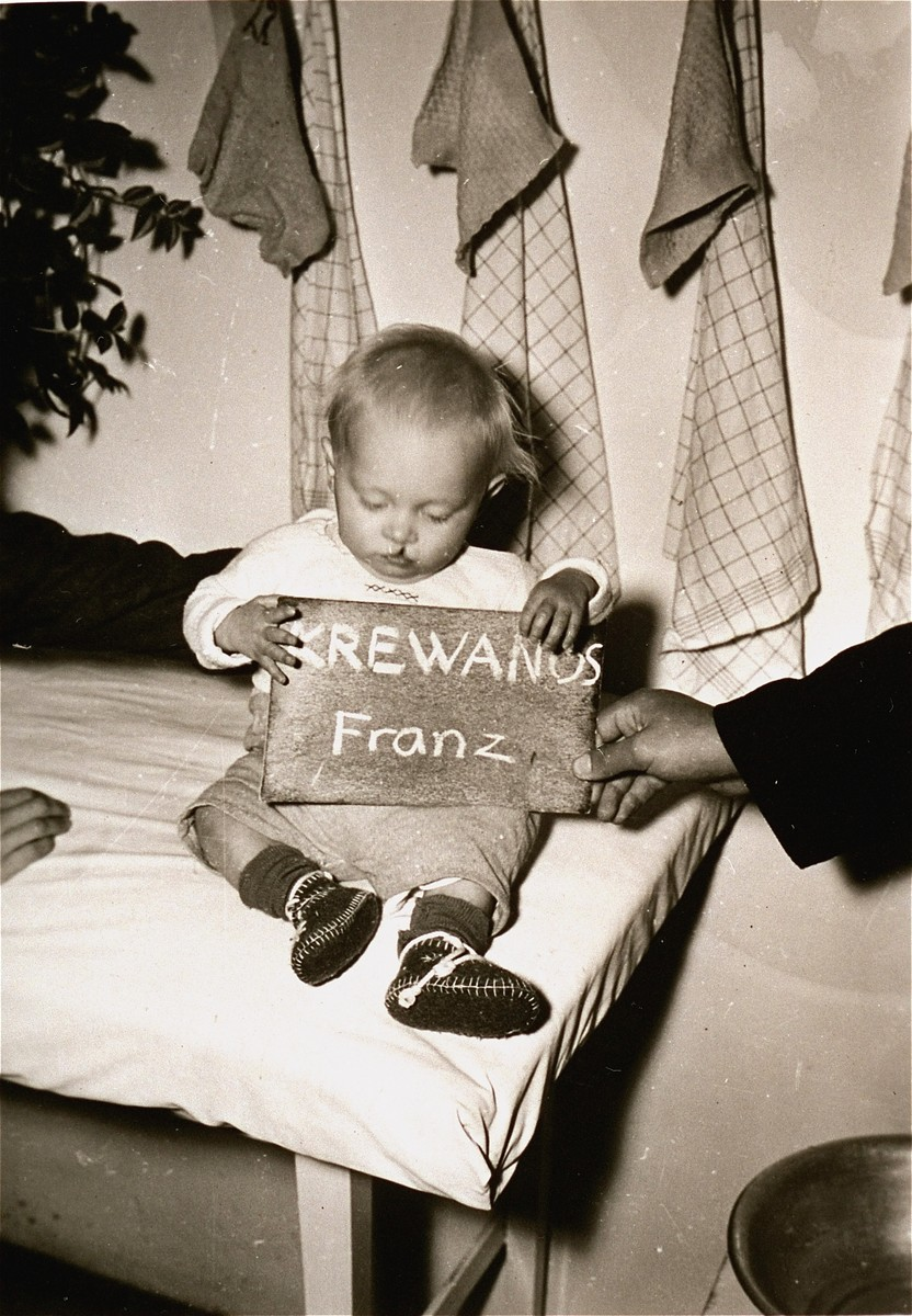 Franz Krewanus holds a name card intended to help any of his surviving family members locate him at the Kloster Indersdorf DP camp.  This photograph was published in newspapers to facilitate reuniting the family.