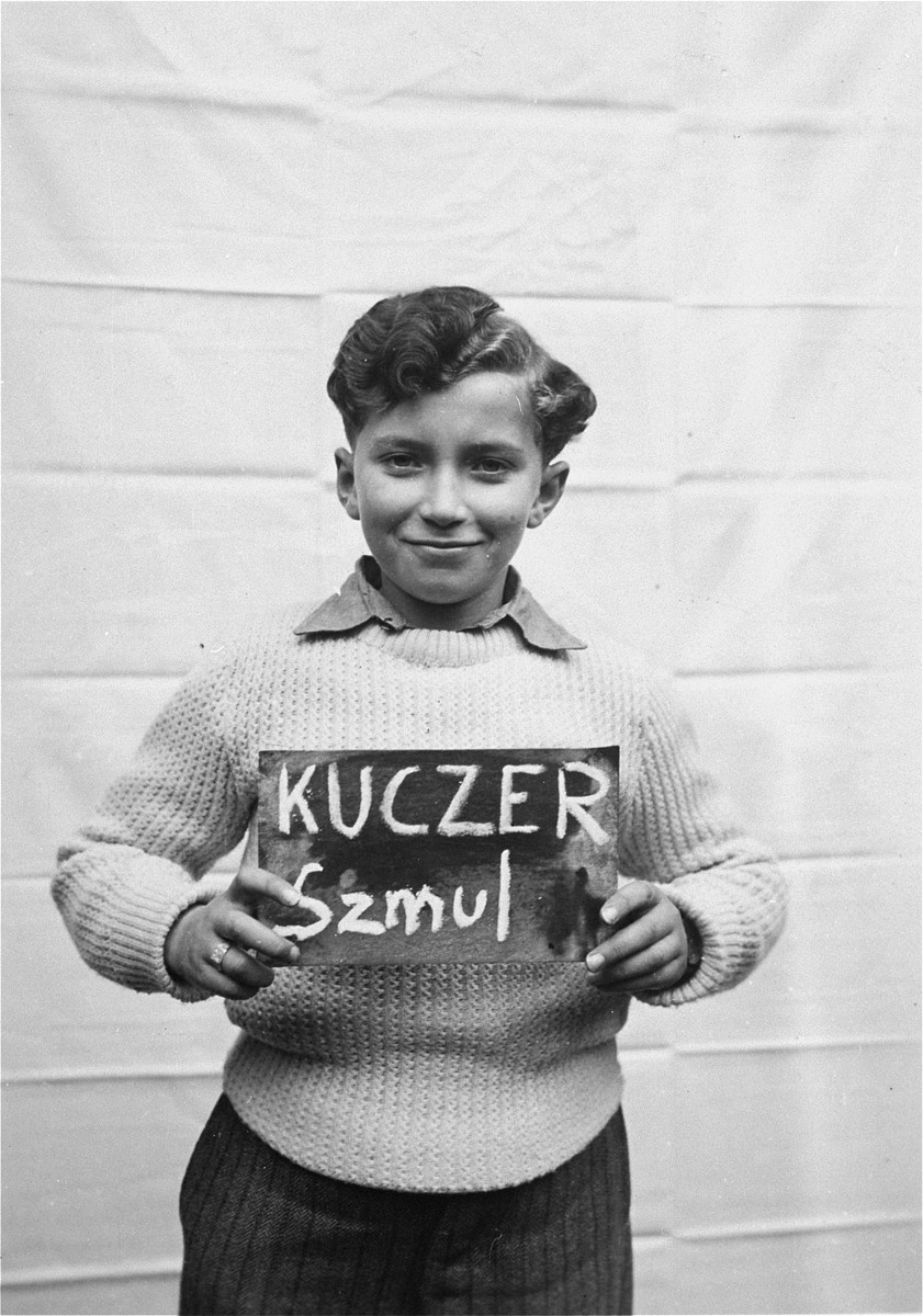 Szmul Kuczer holds a name card intended to help any of his surviving family members locate him at the Kloster Indersdorf DP camp.  This photograph was published in newspapers to facilitate reuniting the family.