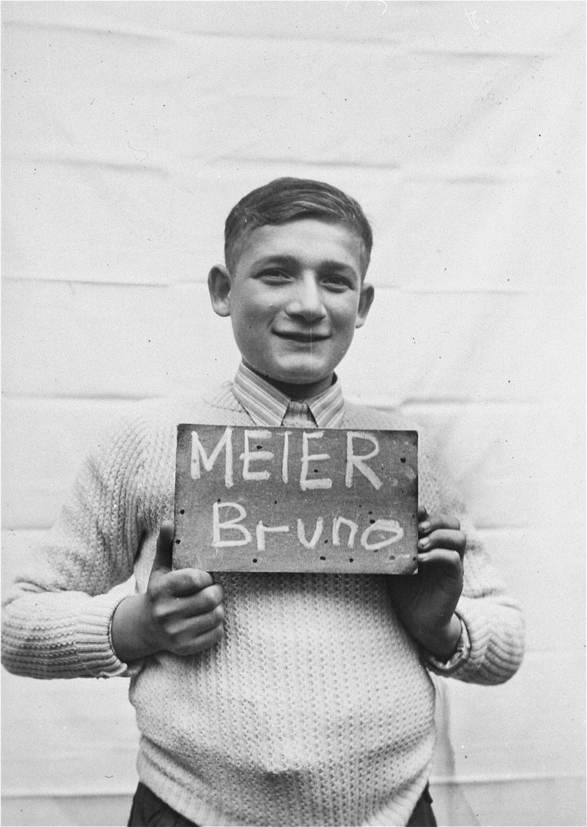 Bruno Meier holds a name card intended to help any of his surviving family members locate him at the Kloster Indersdorf DP camp.  This photograph was published in newspapers to facilitate reuniting the family.