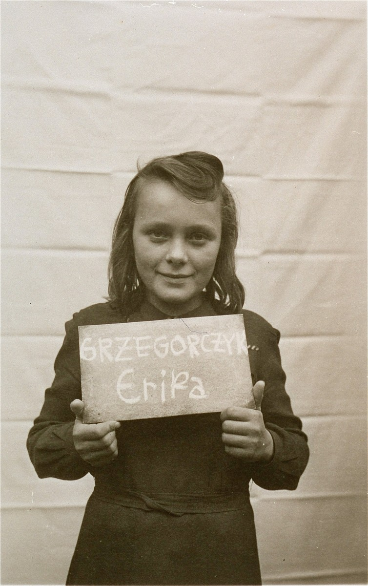Erika Grzegorczyk holds a name card intended to help any of her surviving family members locate her at the Kloster Indersdorf DP camp.  This photograph was published in newspapers to facilitate reuniting the family.