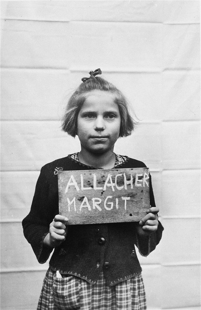 Margit Allacher holds a name card intended to help any of her surviving family members locate her at the Kloster Indersdorf DP camp.  This photograph was published in newspapers to facilitate reuniting the family.