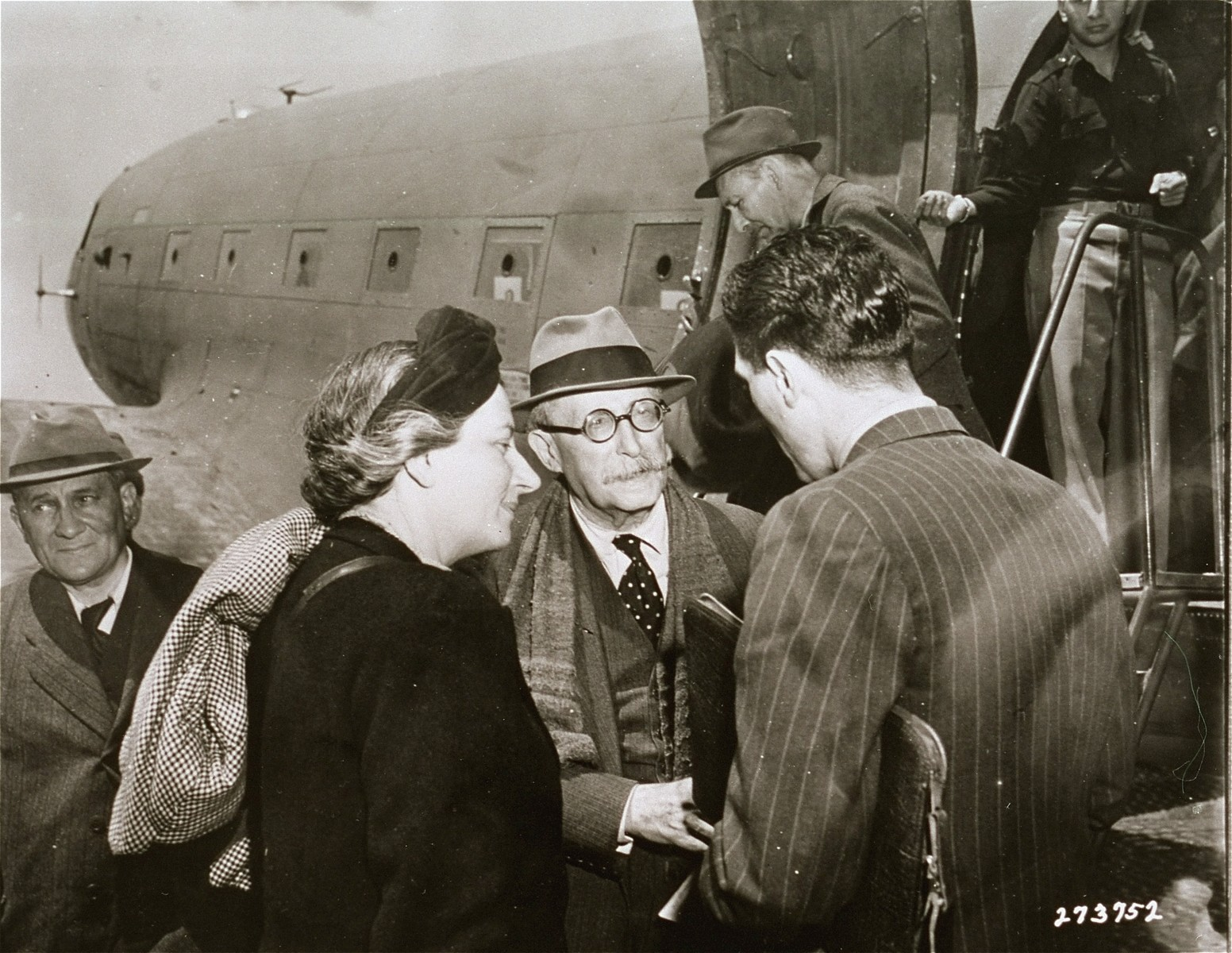 Former French Premier Leon Blum and his wife are greeted by T.S. Estes upon their arrival in Naples aboard an American plane.