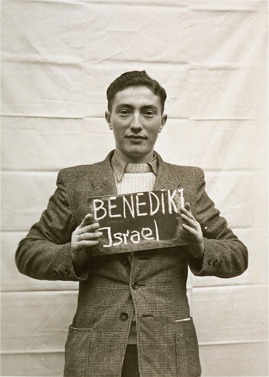 Israel Benedikt holds a name card intended to help any of his surviving family members locate him at the Kloster Indersdorf DP camp.  This photograph was published in newspapers to facilitate reuniting the family.