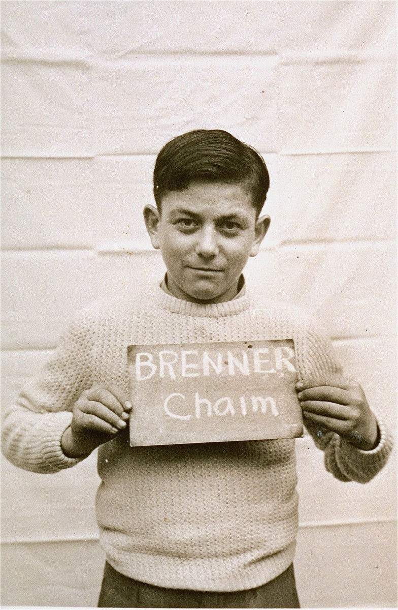 Chaim Brenner holds a name card intended to help any of his surviving family members locate him at the Kloster Indersdorf DP camp.  This photograph was published in newspapers to facilitate reuniting the family.