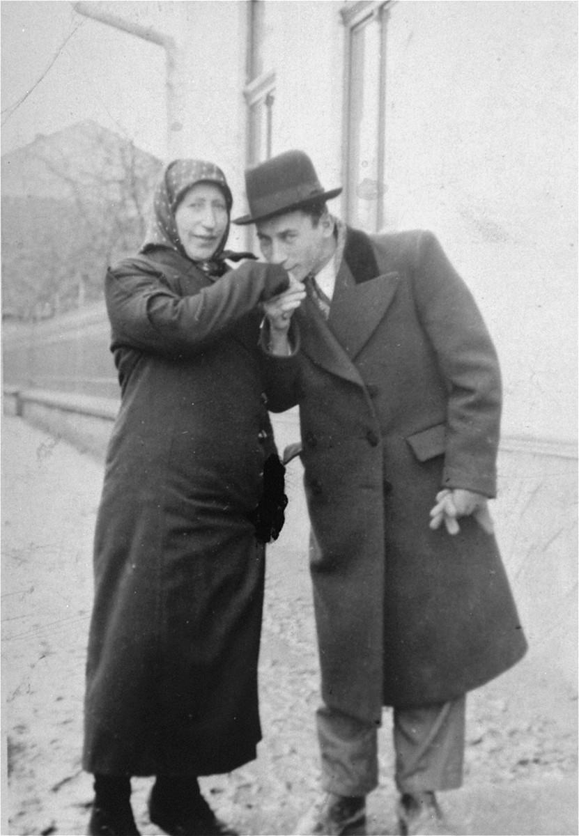 Baruch Nieman kisses the hand of his mother Etta Nieman on a street in Viseul-de-Mijloc, Transylvania.