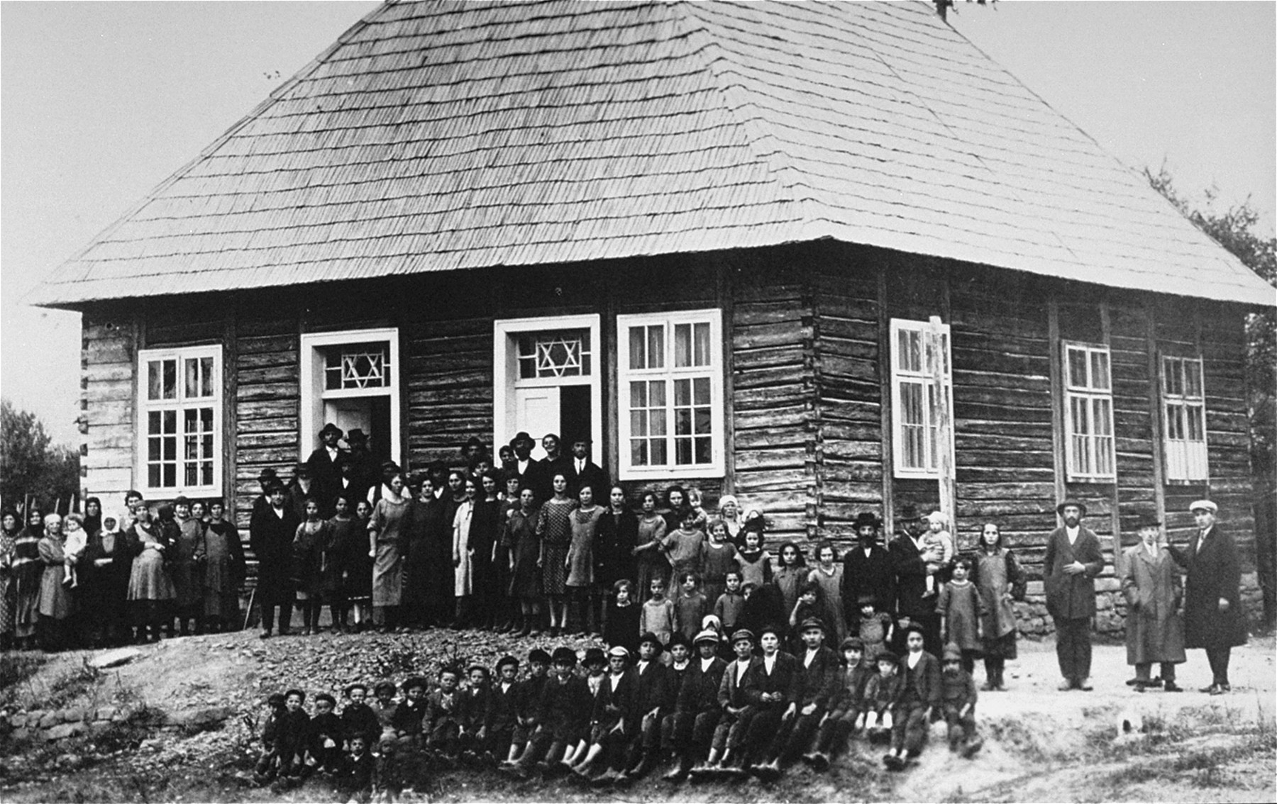 Group portrait of members of the Jewish community of Craciunesti in front of a wooden synagogue.
