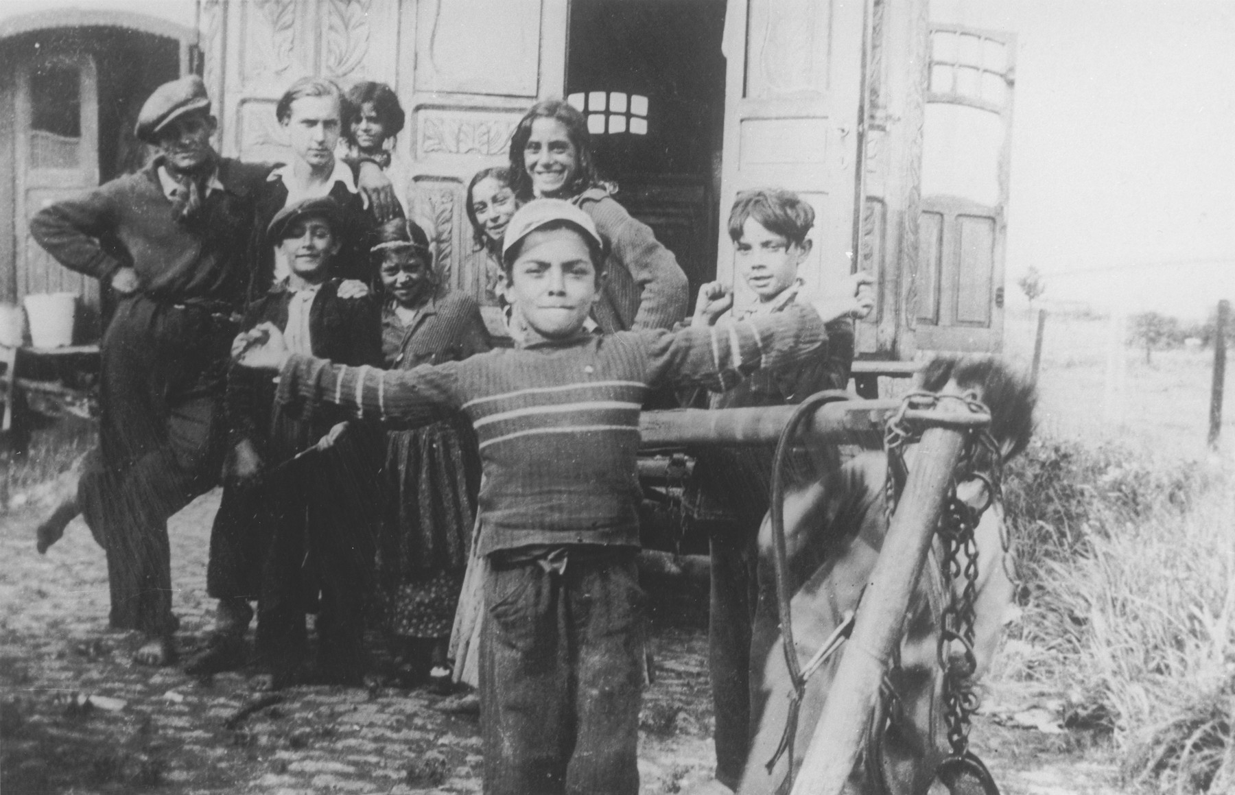 A Roma (Gypsy) child poses in front of a caravan with his arms outstretched, while his family looks on.  Pictured in the back, second from the left, is Jan Yoors.