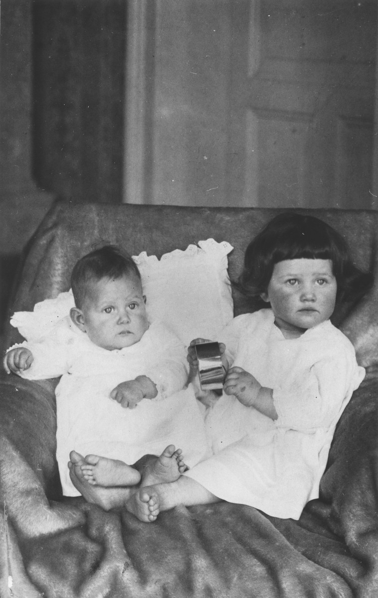 Two young Jewish sisters pose in an armchair in their living room in Bad Homburg, Germany.  Pictured are Judith Feist (left) and her older sister Selma.