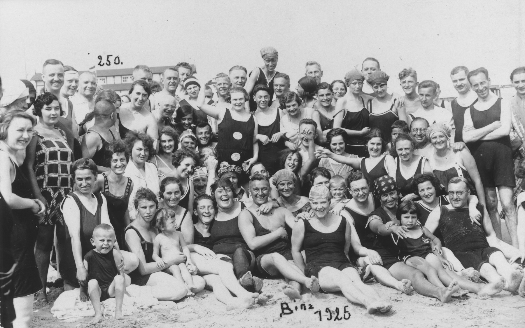 Group portrait of bathers on the beach in Binz, Germany.  Among those pictured is Margarete Schindler Plachte (front row, second from the right, with her arm around a man).