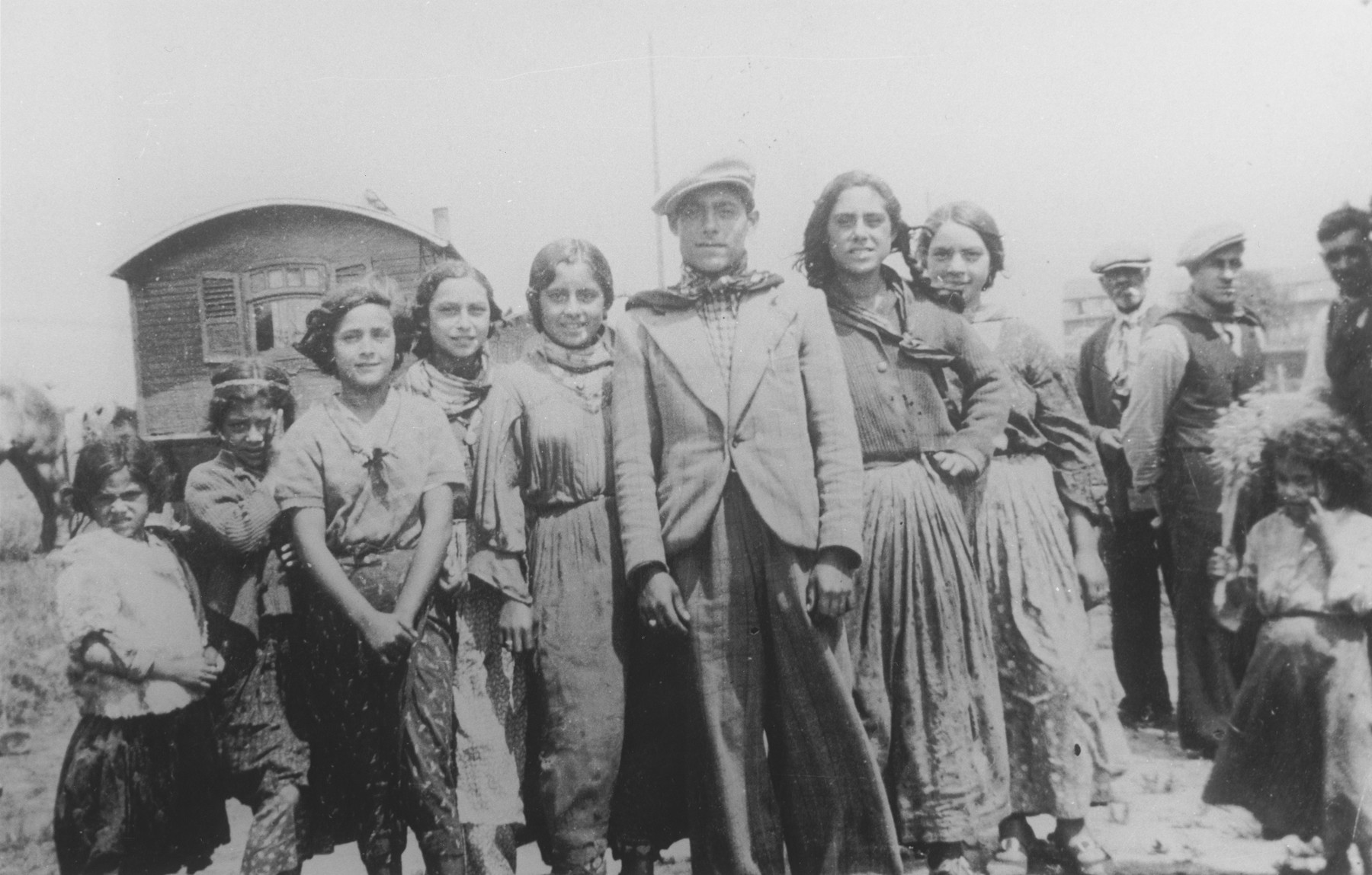 A Gypsy family poses in front of their caravan.