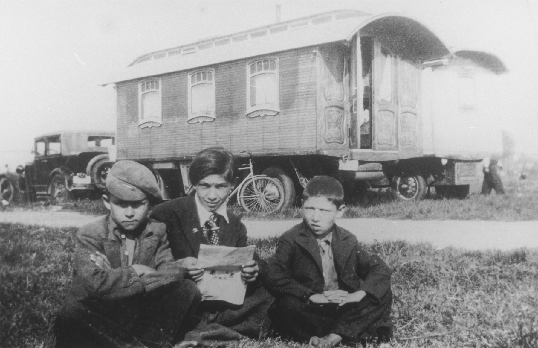 "Three Gypsy brothers sit outside in front of a caravan reading a newspaper.  The caption in ""The Heroic Present"" reads, ""Putzina, Laetshi, and Nanosh, Belgium, 1930s.  These were the first Romani boys encountered by Jan Yoors."""