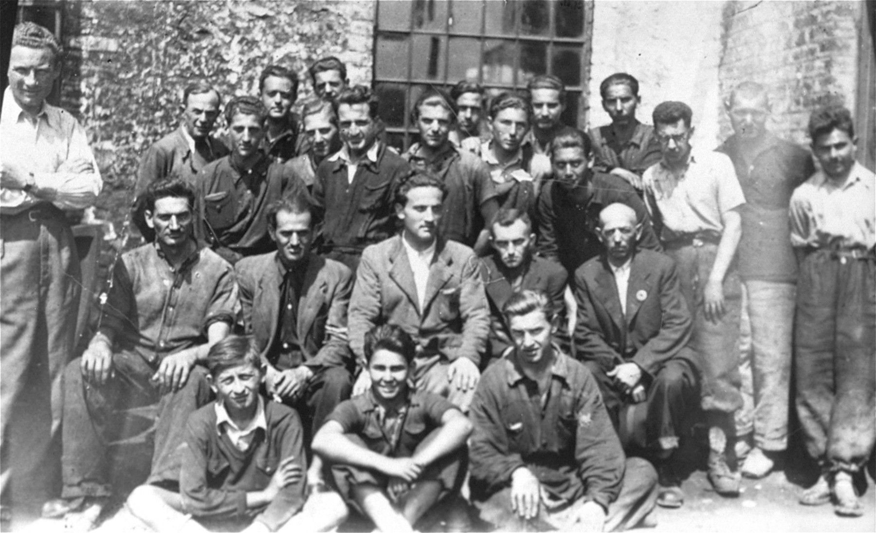 Group portrait of Jewish forced laborers at the Turnatoria, the machine shop established by Siegfried Jagendorf in the Mogilev-Podolskiy foundry.  Pictured in the center is Max Schmidt, an engineer from Cernauti who headed the lathe and power plant department of the Turnatoria.  Also pictured is Max Auslander (standing in the back row, seventh from the left). Friedrich Haas is pictured sitting in the front row center.  Seated in the second row on the far right is the manager, Engineer Josef Schmidt.