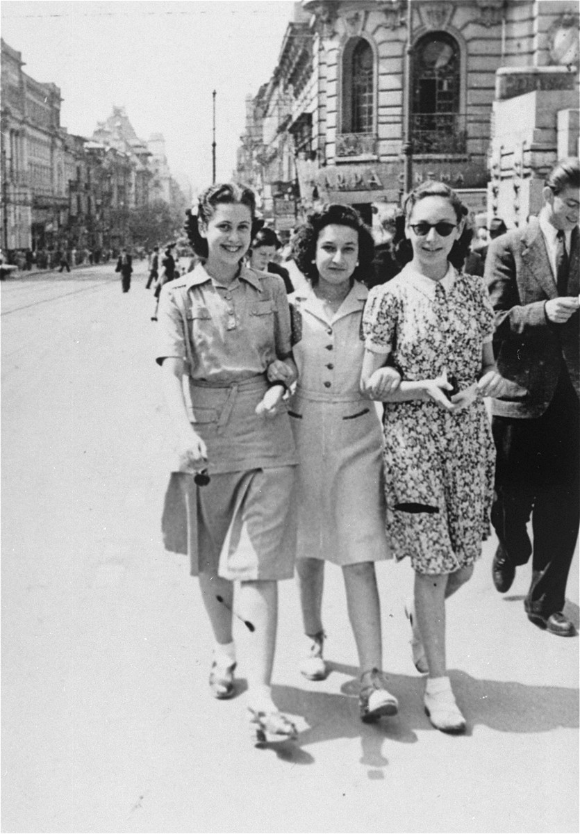 Three Jewish women stroll down a commercial street in Bucharest.    Pictured from left to right are: Valerie Zigmund (Cernes), Jeanine Gutman, and Anna Erlic.