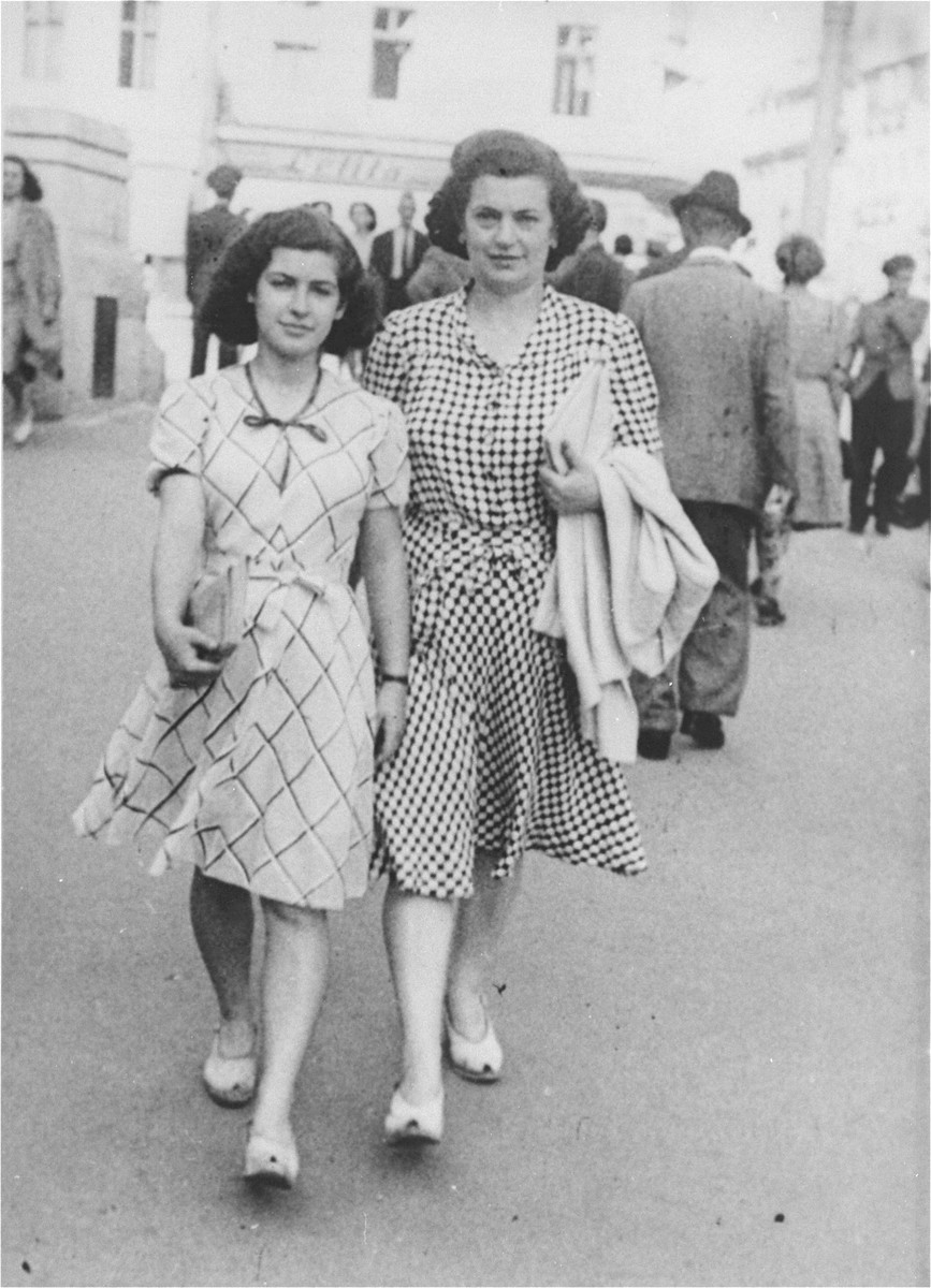 A Jewish mother and daughter walk along a street in Bucharest near the end of the war.  Pictured are Blanka and Marta Kupfermann.