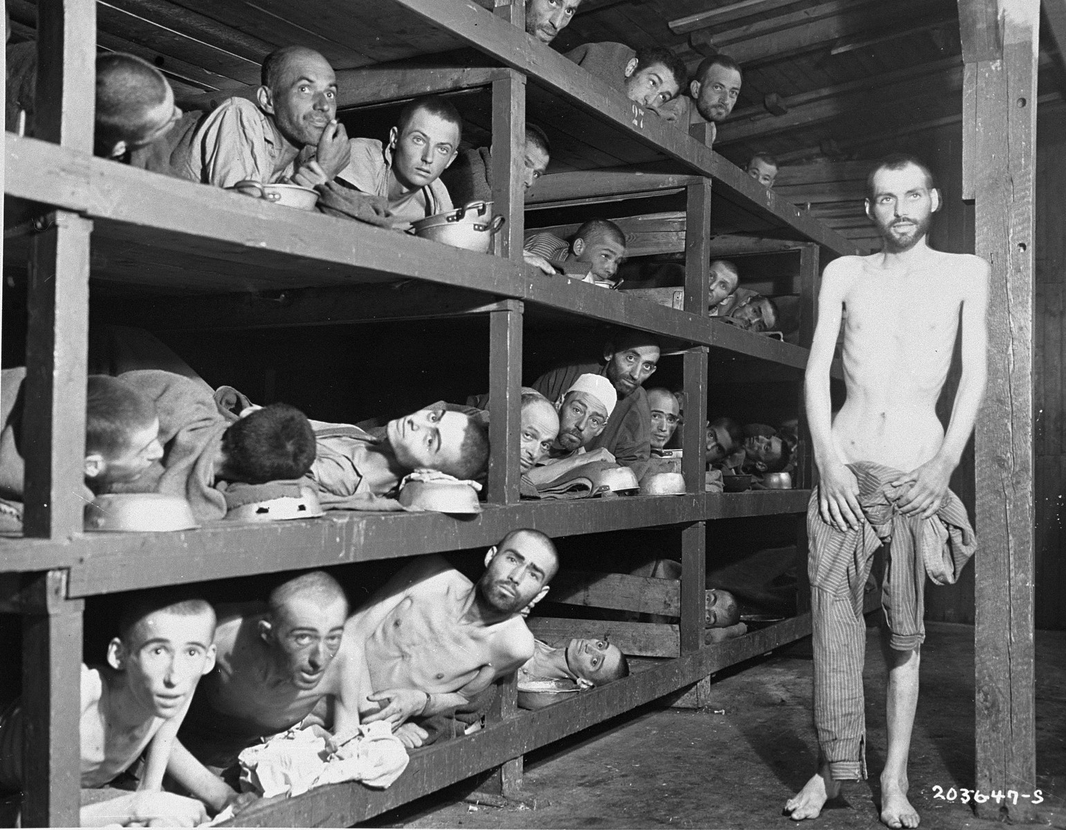 """Former prisoners of the """"little camp"""" in Buchenwald stare out from the wooden bunks in which they slept three to a """"bed.""""    Elie Wiesel is pictured in the second row of bunks, seventh from the left, next to the vertical beam.    The man in the bottom left hand corner has been identified as Michael Nikolas Gruner, originally from Hungary, Gershon Blonder Kleinman or Yosef Reich.  Isaac Reich is in the bottom row, second from the right and Max Hamburger is on the bottom row, fourth from the left.  Perry Shulman from Klimitov, Poland is on the top bunk, second from the left (looking up).  The man in the second row, third from left has been identified as Dawid Najman.  The man in the second row, fourth from the left has been identified as Abraham Hipler;  Berek Rosencajg from Lodz or Zoltan Gergely from Cluj.  The man on the third bunk from the bottom, third from the left, has been identified alternatively as Ignacz (Isaac) Berkovicz, Abraham Baruch and Joseph Icovic )from Tecovo) .  Juraj (now Naftali) Furst is pictured in the third bunk, fifth from the left. Standing on the right is Chaim David Halberstam.  In the top left bunk, far right is Oscar Kleinshpitz (later Haberkorn).    Original caption reads:  """"Slave laborers  pedred from their tomb-like, wooden bunks at the concentration camp at Buchenwald, near Weimar, Germany, when U.S. troops liberated the area.  Approximately 21,000 inmates - Russian, Polish, French, Italian, and Czechoslovakian - were freed.  They were described as """"the living dead"""".  The camp doctors agreed that a t least 6,000 inmates had died as the result of German brutality during March, 1945.  In the Winter of 1939, the prisoners died at the rate of 900 daily.  In 10 years, more than 70,000 persons were starved and butchered in this atrocity center."""""""