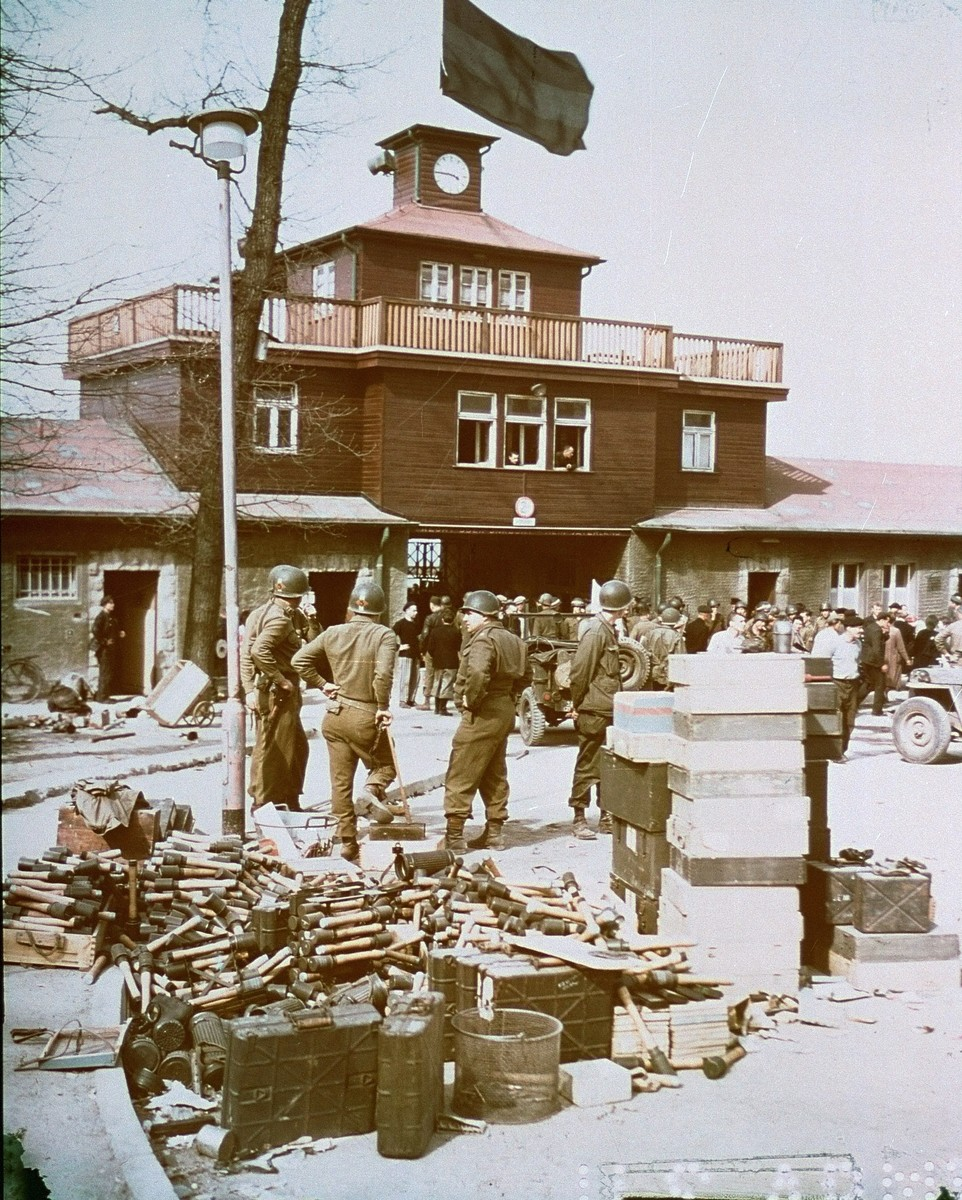American soldiers with a stockpile of German arms and ammunition at the gate to Buchenwald. The ammunition was part of a cache of arms taken from SS guards. Survivors in the background are being transported to a DP camp, where they will be segregated according to nationality, and await repatriation.