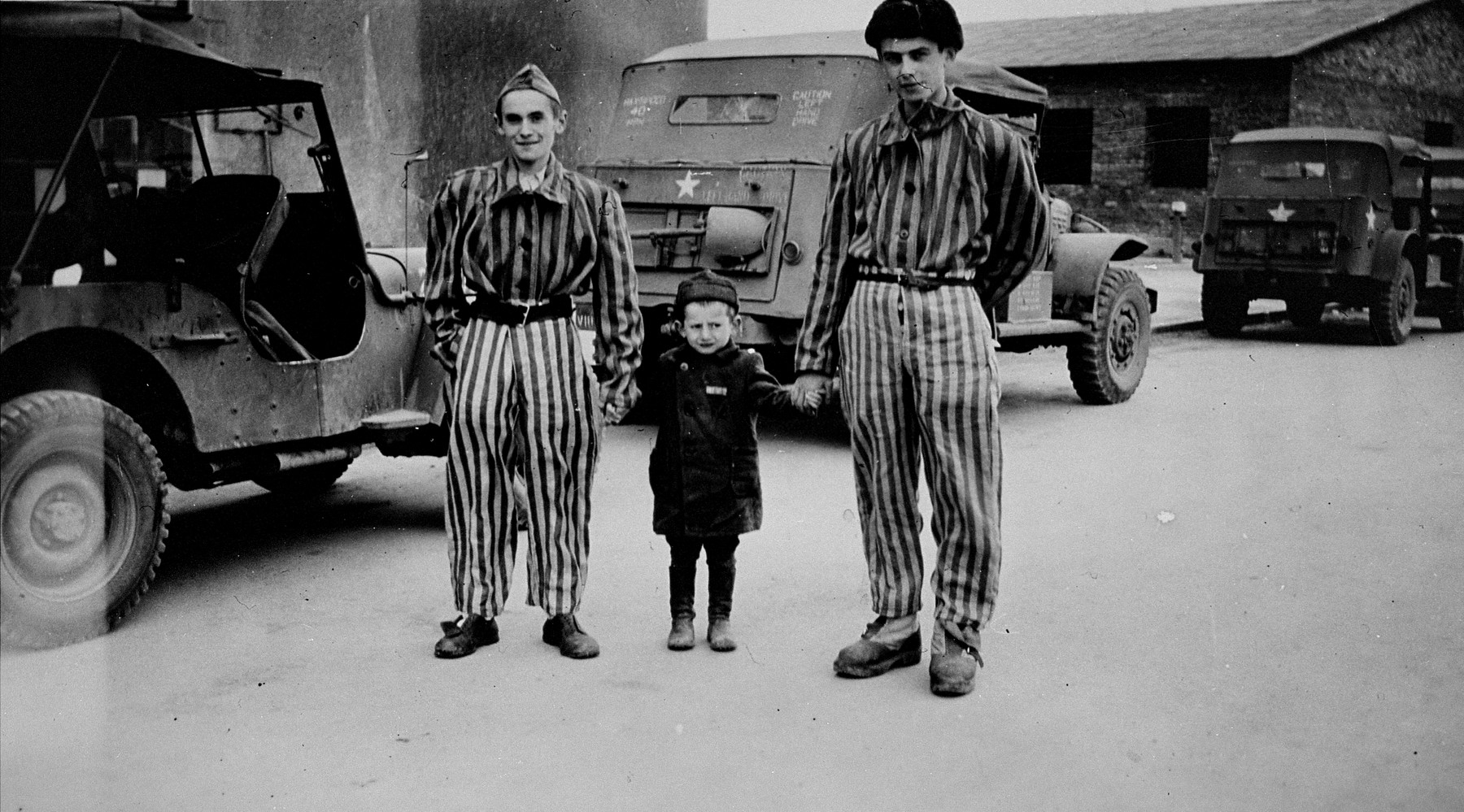 """Child survivor Joseph Schleifstein (center) poses with two young men wearing concentration camp uniforms in Buchenwald.  The original caption reads """"The little boy, was four years old, had been in Buchenwald 3 years -- a political prisoner."""""""