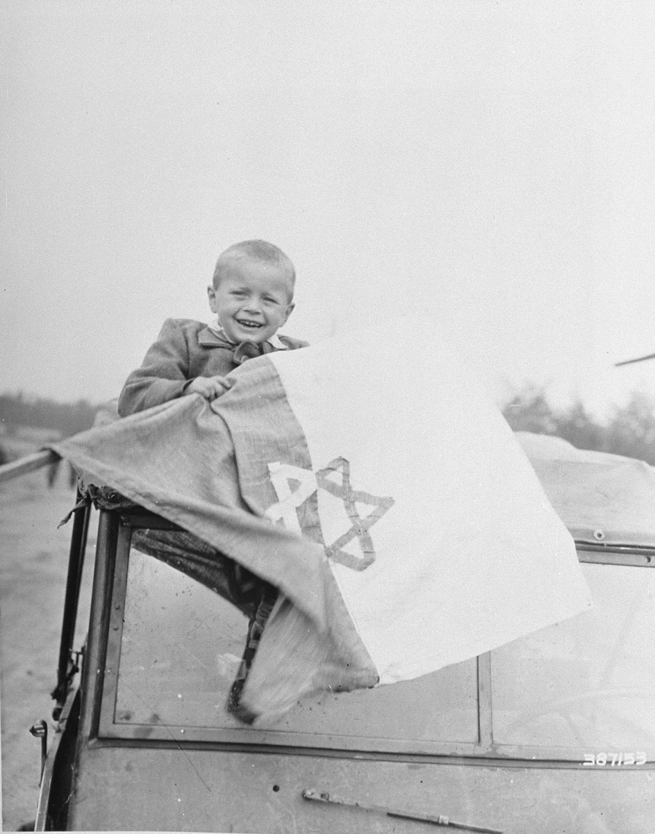 Five year-old Briner Odon sits on top of an American jeep holding a Star of David flag just prior to his departure from Buchenwald to France.  Odon, whose mother and father were shot by the Nazis, is one of a group of Jewish orphans released from Buchenwald concentration camp and sent to France.  From there, some will travel to Palestine and some to America.